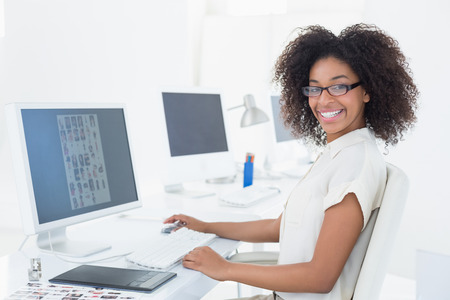 Smiling casual editor working at desk in her office
