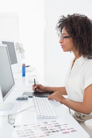 digitizer: Pretty photo editor using digitizer at desk in her office