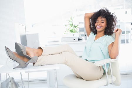 Happy businesswoman sitting with her feet up in her office photo
