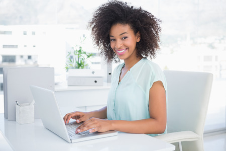Happy businesswoman working on her laptop in her office Stock Photo