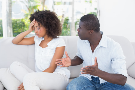 Attractive couple having an argument on couch at home in the living room photo