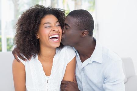 pareja besandose: Atractivo hombre besando a su novia en la mejilla en su casa en la sala de estar