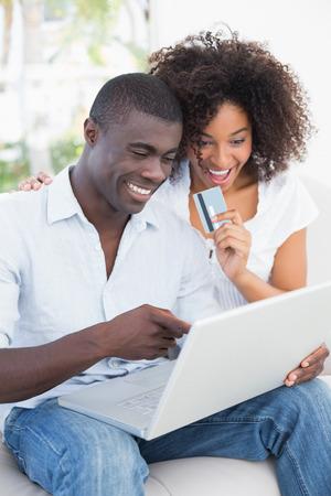 verliefd stel: Aantrekkelijk paar met behulp van laptop samen op de sofa om online te winkelen thuis in de woonkamer Stockfoto