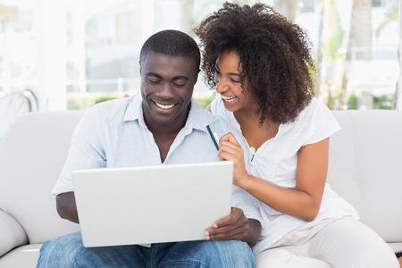parejas de jovenes: Atractiva pareja utilizando el port�til en el sof� junto a la tienda en l�nea en casa, en la sala de estar Foto de archivo