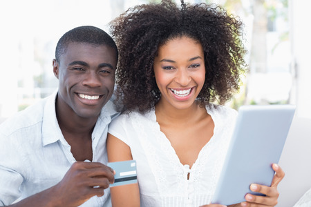 man holding money: Attractive couple using tablet together on sofa to shop online at home in the living room