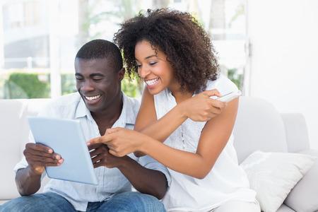 black guy: Atractivo joven sentado en el sof� mirando juntos el tablet como en casa en la sala de estar