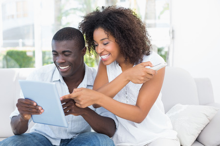 couches: Attractive couple sitting on couch together looking at tablet at home in the living room Stock Photo