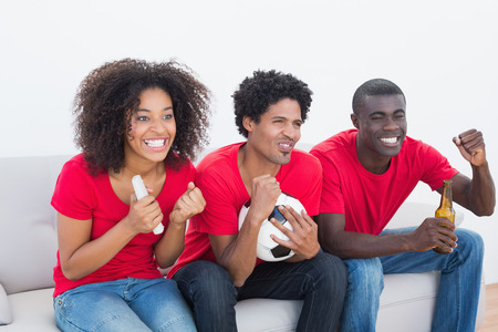 Football fans in red sitting on couch cheering on white background photo