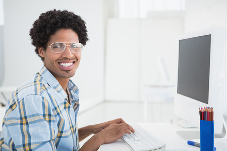 Young designer working at his desk smiling at camera in his office photo