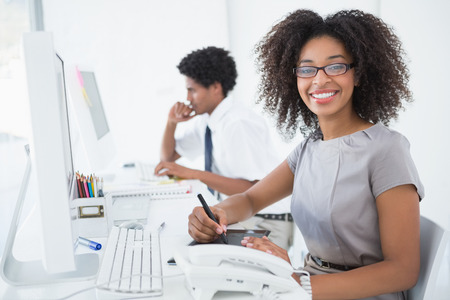 business men: Young pretty designer smiling at camera at her desk in her office Stock Photo