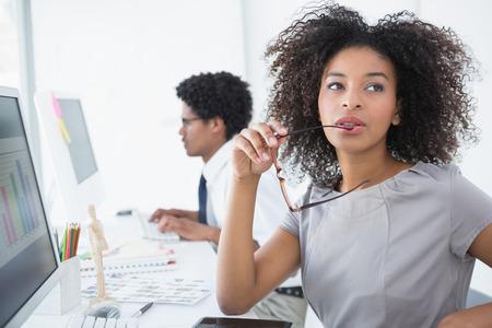 mannequin africain: Jeune pensée de l'éditeur à son bureau dans le bureau de création