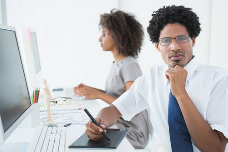 Young designer looking at camera at his desk in creative office photo