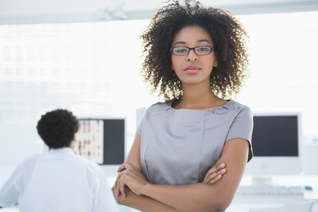 Young pretty editor looking at camera with colleague working behind her in creative office photo