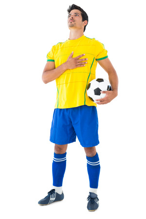 anthem: Football player in yellow with ball listening to anthem on white background Stock Photo