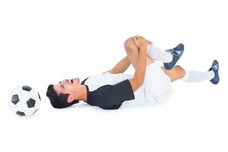 Football player in white lying injured on white background photo