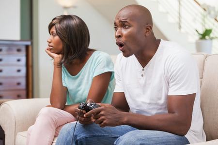 Bored woman sitting next to her boyfriend playing video games at home in the living room photo