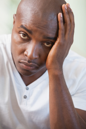 desolación: Malestar hombre sentado en el sofá mirando a la cámara en casa, en la sala de estar