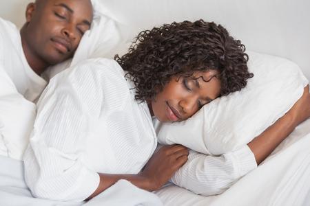 自宅の寝室のベッドで一緒に眠っている幸せなカップル