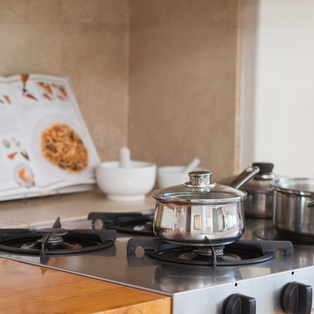 Stove top with saucepan and recipe book at home in the kitchen photo