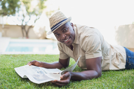 Smiling man relaxing in his garden reading newspaper on a sunny day photo