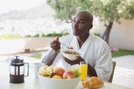 comiendo cereal: Hermoso hombre en bata de ba�o tomando el desayuno al aire libre en un d�a soleado