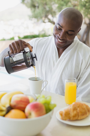 Handsome man in bathrobe having breakfast outside on a sunny day photo