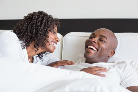 Happy couple cuddling in bed and laughing at home in the bedroom Stock Photo