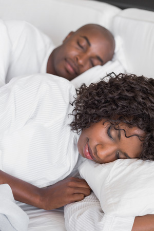 Happy couple lying in bed together sleeping at home in the bedroom Stock Photo