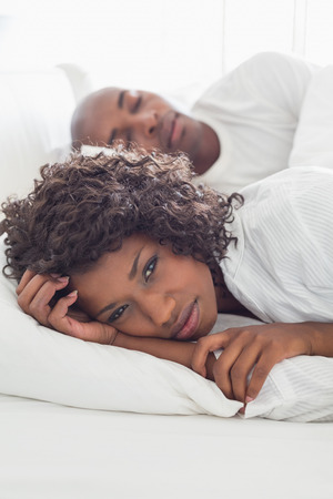 gloominess: Upset woman lying in bed with sleeping boyfriend at home in the bedroom Stock Photo