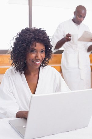 Pretty woman in bathrobe using laptop at table with partner in background at home in the kitchen photo