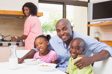 niños cocinando: Feliz familia desayunando juntos en la mañana en su casa en la cocina