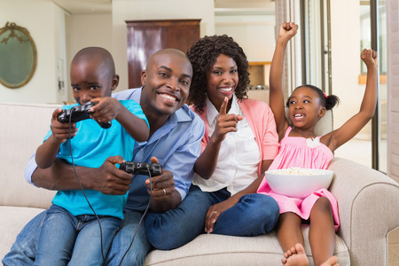 Happy family relaxing on the couch playing video games at home in the living room photo