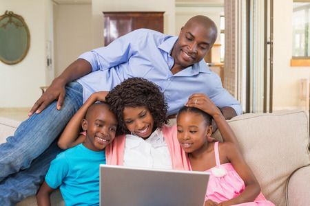 multiracial family: Happy family relaxing on the couch using laptop at home in the living room
