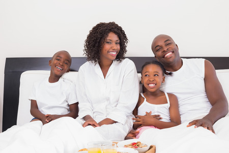 Happy family having breakfast in bed at home in the bedroom photo