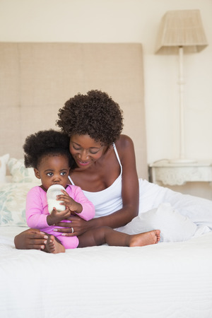 babygro: Happy mother and baby girl sitting on bed together at home in the bedroom Stock Photo