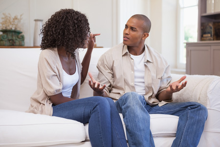 couples people: Unhappy couple arguing on the couch at home in the living room