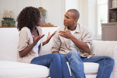 Unhappy couple arguing on the couch at home in the living room Stock Photo - 30926088