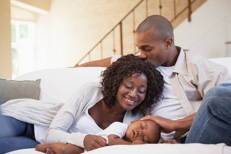 babygro: Baby boy sleeping peacefully on couch with happy parents at home in the living room Stock Photo