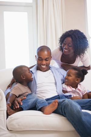 famille africaine: Famille heureuse assis sur le canap� ensemble � la maison dans le salon