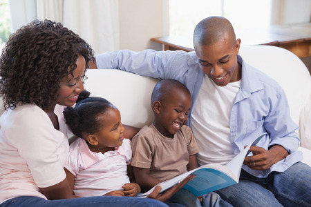 Happy family sitting on couch together reading book at home in the living room photo