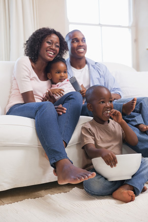 Happy family sitting on couch together watching tv at home in the living room photo