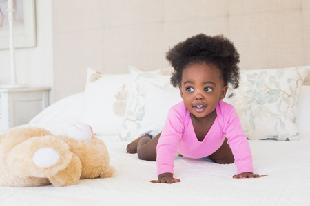 babygro: Baby girl in pink babygro crawling on bed at home in the bedroom Stock Photo
