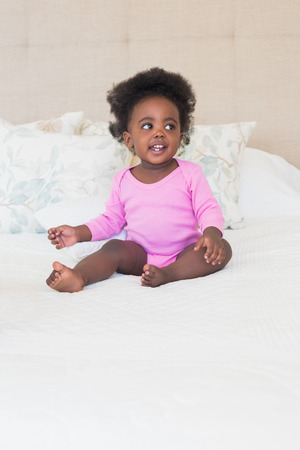babygro: Baby girl in pink babygro sitting on bed at home in the bedroom Stock Photo