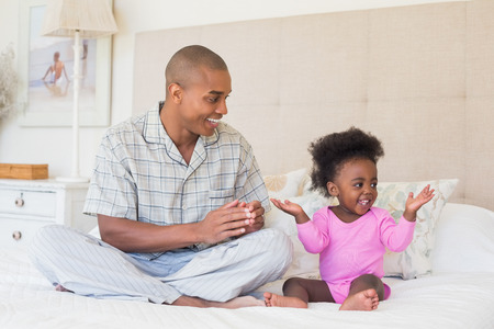 babygro: Happy father and baby girl sitting on bed together at home in the bedroom