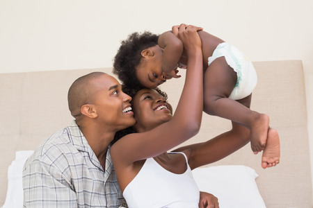 baby diaper: Happy couple on bed with baby daughter at home in the bedroom Stock Photo