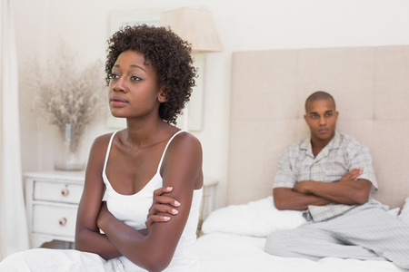Unhappy couple not speaking to each other on bed at home in the bedroom photo