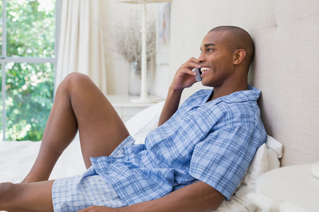Happy man lying on bed and talking on phone at home in the bedroom photo