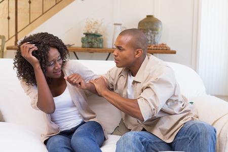 pareja enojada: Hombre enojado agarrando su socio miedo en el sofá en casa, en la sala de estar