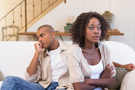 Unhappy couple not speaking to each other at home in the living room photo