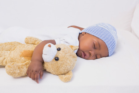 babygro: Adorable baby boy sleeping peacefully with teddy at home in the living room